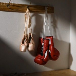 Boxing gloves and ballet shoes hanging in dressing room